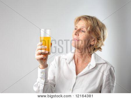 Senior woman holding a glass of orange juice