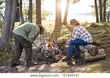 Senior Man Putting Wood On Camp Fire