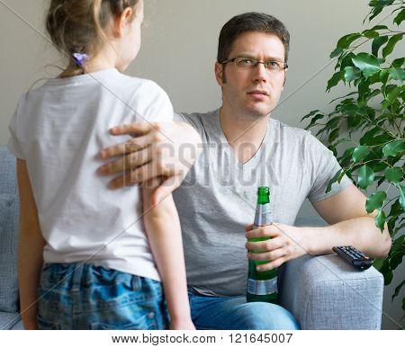 Little girl disturbing her dad while he is watching TV.
