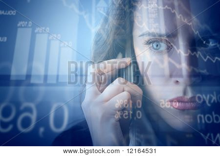 Worried businesswoman making a phone call with stock exchange graphics on the background