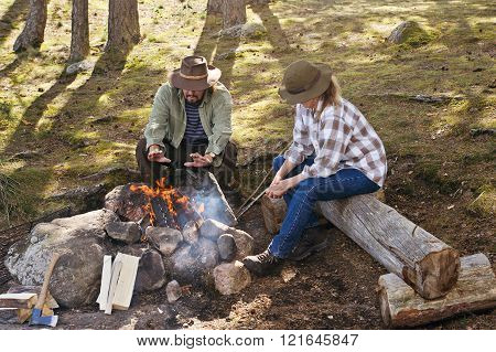 warming hands at camp fire
