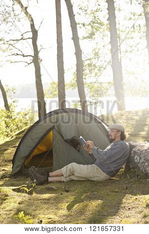 Senior man sits outside a tent and reads a book. there's difital filter lens flare