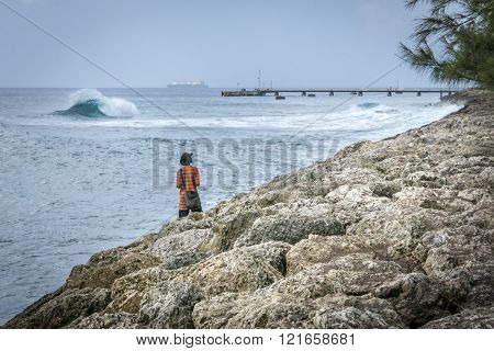 BRIDGETOWN BARBADOS 21 DECEMBER 2015 - Man on the shore watching the waves breaking in the sea on a windy day at Bridgetown Barbados