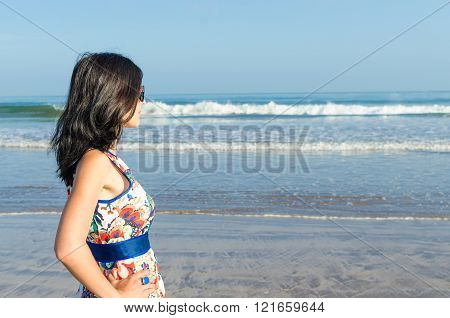 Young girl in beautiful dress looking at the ocean and city
