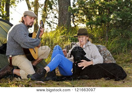 Senior couple enjoying some music outside their tent in evening light. Man plays guitar and they sing together. They have their pet curly coated retriever with them