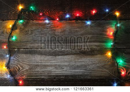 Frame of the colorful Christmas festoon on the wooden board