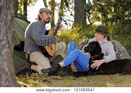 Senior couple enjoying some music outside their tent in evening light. Man plays guitar and sings. They have their pet curly coated retriever with them
