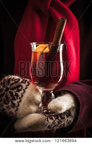 Mulled whine with spices in the hands in knitted mittens vertical