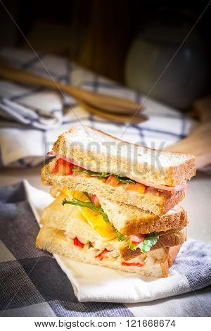 Sandwich on wood table with spot lighting.