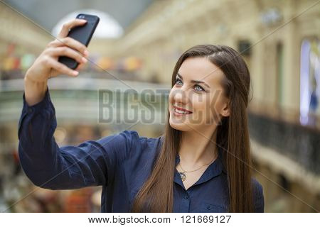 Young beautiful brunette girl taking selfie with mobile phone, in shop