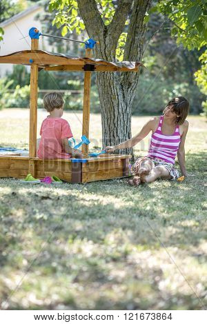 Young mother playing with her toddler son sitting in a sandbox under a tree on a sunny summer day. ** Note: Shallow depth of field