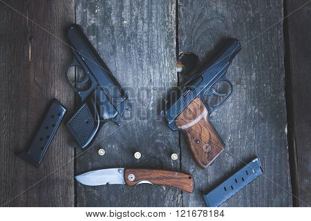 Weapons On The Background Of A Wooden Table
