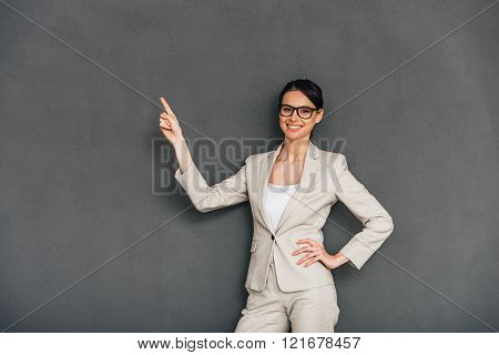 Take a look here! Cheerful young businesswoman in glasses pointing on copy space and looking at camera with smile while standing against grey background
