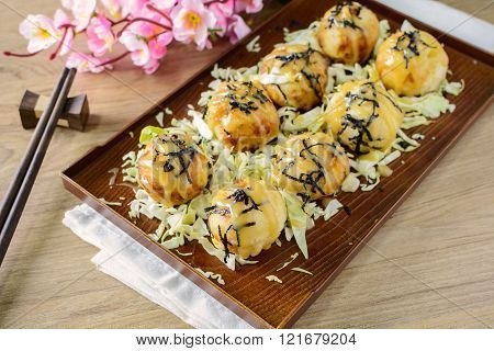 Close up of takoyaki on wooden table with chopsticks, Japanese food