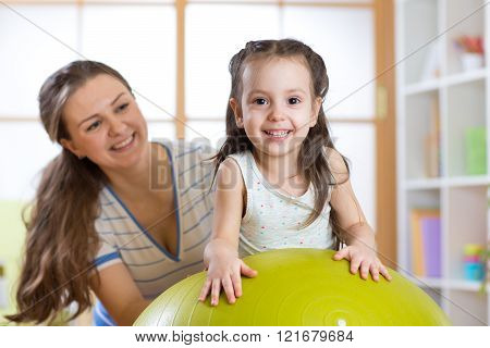 mother and her child having fun with gymnastic ball