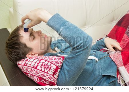 Ill man checking temperature, lying on sofa