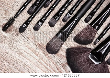 Set of various natural bristle makeup brushes: for applying foundation blush eyeshadow fan brush and others. Professional tools of make-up artist on shabby wooden surface poster