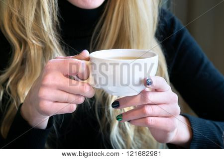 Woman Holding Cup Of Tea In A Cafe