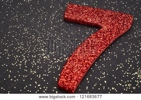 Number Seven Red Color Over A Black Background. Anniversary