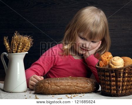 The child, a girl at the table. On the table a loaf of rye pumpernickel