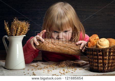 Child smelling a loaf of rye pumpernickel