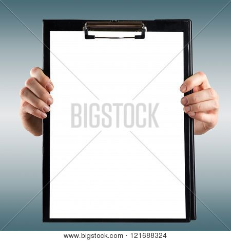 Female doctor's hand holding medical clipboard with blank sheet of paper on blie blurred background.