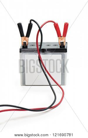 A Car battery with red and black battery Jumper or booster cables with copper clamps attached to the terminals. Automotive battery isolated on white.