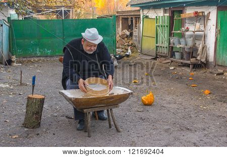 Country man doing daily work (meal screen fines) at the homestead - central Ukraine, Europe