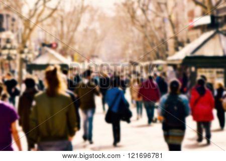 defocused blur background of people walking in a busy pedestrian street