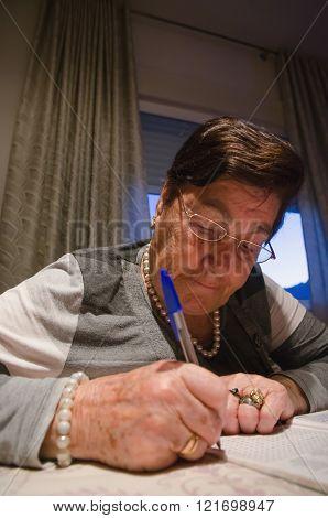 Portrait Of Senior Woman With Crossword Puzzle