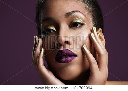 Woman With Golden Eye Makup And Violet Lips