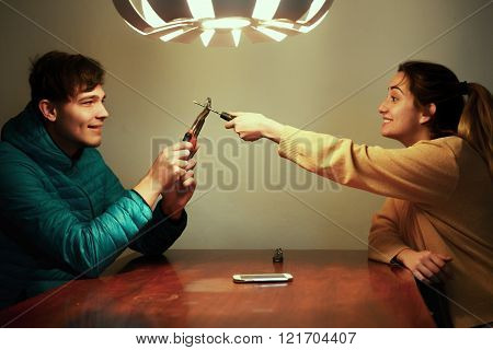 Friends fooling, man and woman playing with pliers and screwdriver. Fun, positive emotions