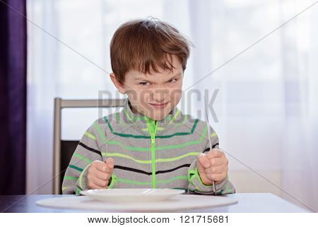 hungry boy child waiting for dinner. Holding fork and knife in his hands