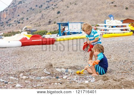 Two little kid boys playing on beach with stones