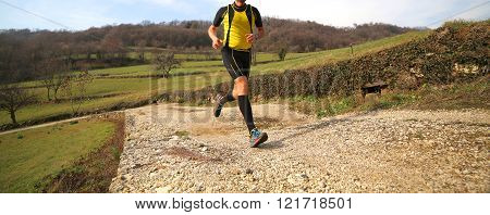 Runner With Sneakers Runs On Country Road During The Cross Country Race