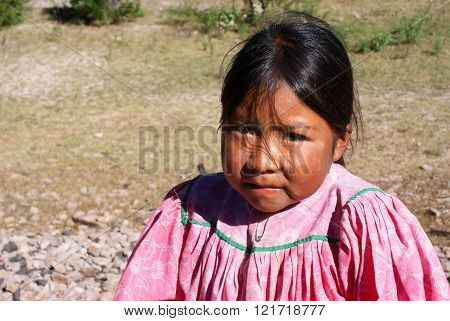 Creel, Mexico - October 9, 2014: Indigenous Tarahumara girl is seen wearing traditional bright outfit in Copper Canyons, Chihuahua, Mexico on October 9, 2014
