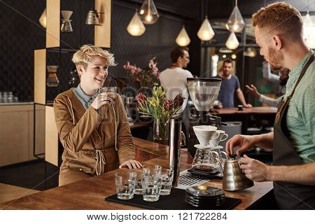 Blonde young woman sitting at the counter of a modern coffee shop with a cup of coffee, smiling while listening to the barista talking and making filter coffees