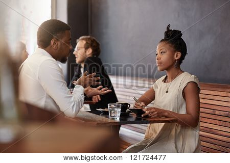 Beautiful African woman taking notes while having a business meeting with and African man in a modern cafe, which is busy with other customers