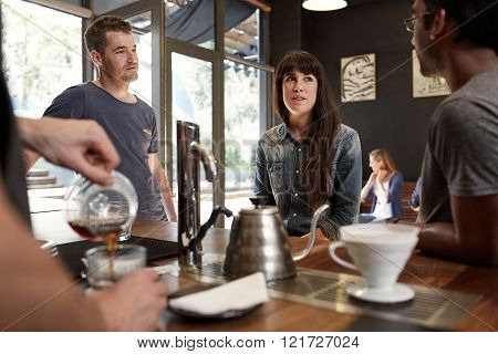 Two guys and a girl who are friends having a chat while waiting for their coffee at the counter of a trendy, modern coffee shop, with a barista pouring coffee in the foreground ** Note: Visible grain at 100%, best at smaller sizes