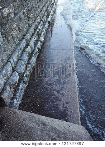 Sea wall pathway and waves beach seascape photographed at Teignmouth in Devon poster