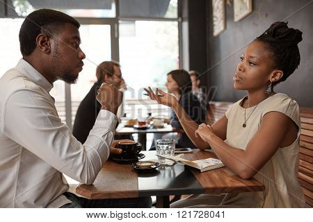 African businesswoman and businessman sitting at a small table in a busy modern cafe, discussing ideas over coffee