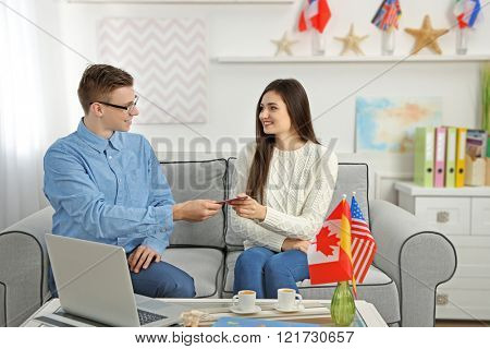 Agent giving passport and ticket to young woman in the office of travel company