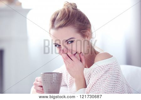 Blonde beautiful smiling girl enjoying her cup of hot delicious coffee
