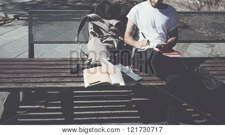 Hipster wearing white tshirt sitting city park bench and writing textbook. Studying at the Universit