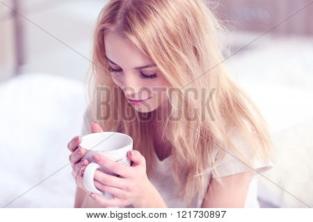 Attractive young blonde girl sitting in bed