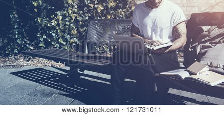 Man wearing white tshirt sitting city park and reading book. Studying at the University, working new