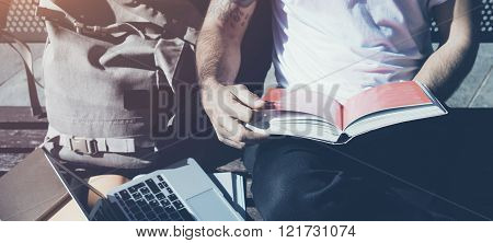 Closeup photo man wearing white tshirt sitting city park bench and reading book. Studying at the Uni