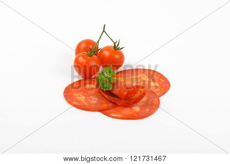 slices of chorizo salami and cherry tomatoes on white background