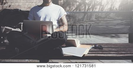 Photo man sitting city park bench and using laptop wireless internet. Studying at the University, wo