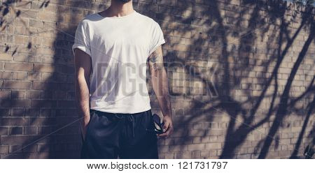 Photo style man with tattoo wearing blank white tshirt. Stands in front of a brick wall. City street